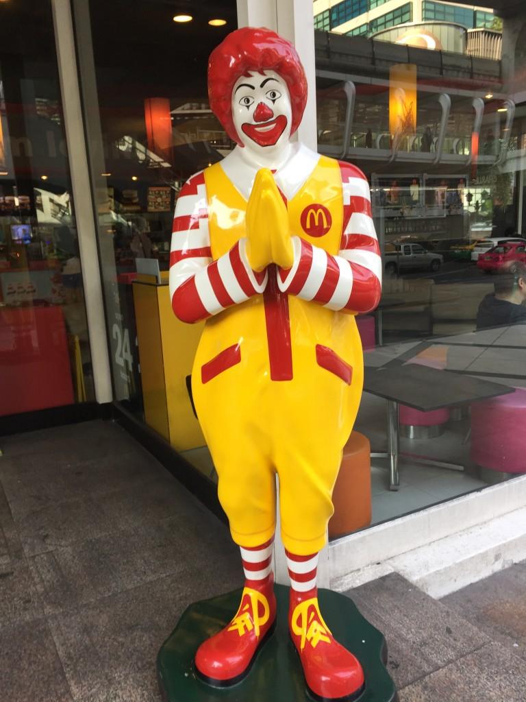 マクドナルドの店頭で両手を合わせるドナルド人形